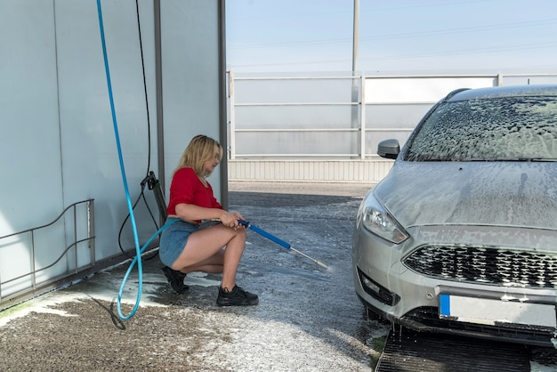 Donna che pulisce la sua auto con getto d'acqua con schiuma su autolavaggio self-service
