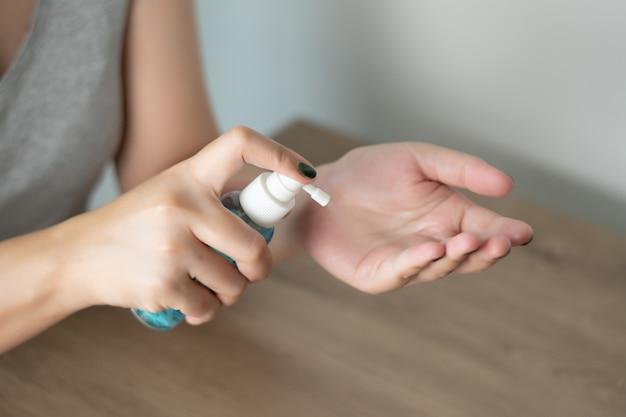 Donna che pulisce il virus disinfettante per le mani e previene il virus covid-19 che spruzza gel o antibatterico