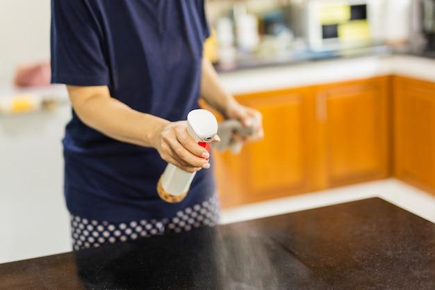 Donna che pulisce la superficie del tavolo da cucina con flacone spray disinfettante.
