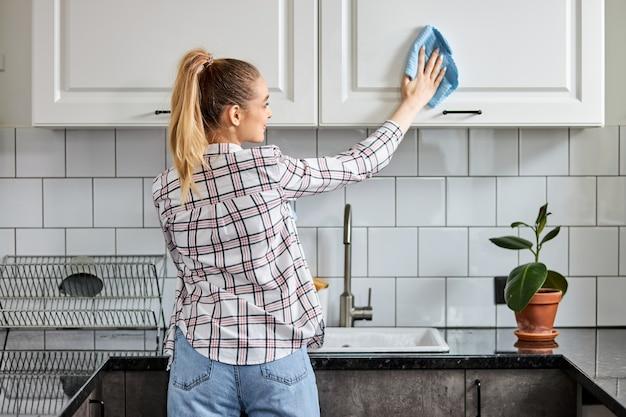 Donna che pulisce la cucina con detergente spray e strofinaccio, concetto di igiene. femmina bionda in abiti casual che puliscono la cucina moderna. lavori di casa. pulizia della casa. retrovisore
