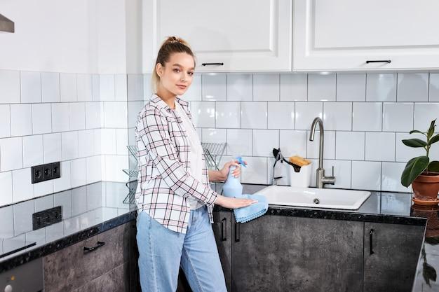 Donna che pulisce la cucina con detergente spray e strofinaccio, concetto di igiene. femmina bionda in abiti casual che puliscono la cucina moderna, guarda la posa della fotocamera. lavori di casa. pulizia della casa