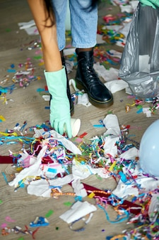 Donna che pulisce il disordine del pavimento nella stanza dopo la festa, rimuove la spazzatura dal pavimento, tazze usa e getta in un sacchetto, la mattina dopo la celebrazione della festa, lavori domestici, servizio di pulizia