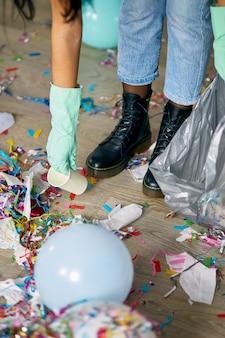 Donna che pulisce il disordine del pavimento in camera dopo la festa, rimuove l'immondizia dal pavimento