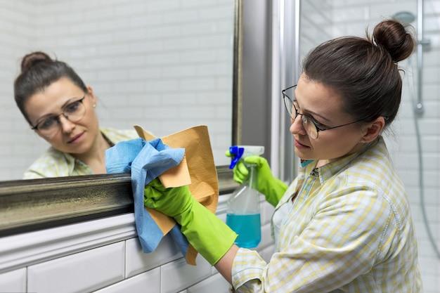Donna che pulisce lo specchio in bagno usando uno straccio professionale e uno spray per il lavaggio, primo piano