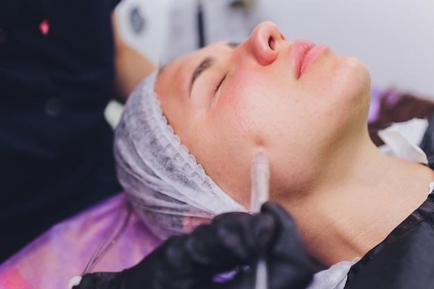 Donna che pulisce i pori della pelle del naso usando il dispositivo di rimozione dei punti neri sotto vuoto, procedura cosmetica.