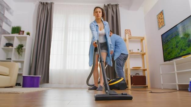 La donna pulisce il pavimento usando l'aspirapolvere e il marito usando la scopa.