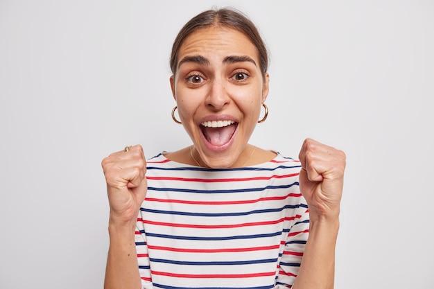 La donna stringe i pugni grida per la sua squadra preferita mentre guarda la partita di calcio incoraggia vestita con un maglione a strisce casual su bianco
