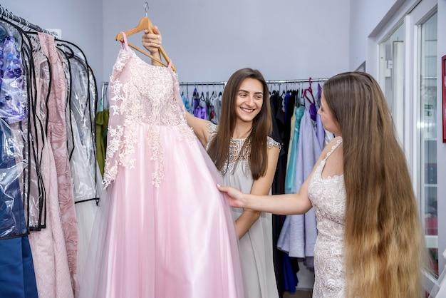 Cliente della donna che esamina vestito nel negozio di abbigliamento