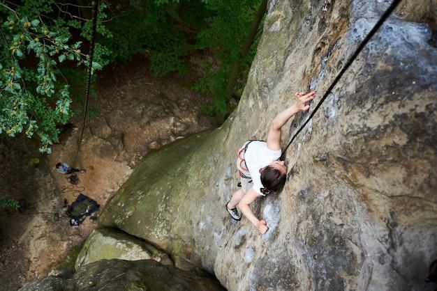 Donna arrampicata su roccia con corda