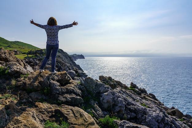 Donna che si arrampica su una pietra a braccia aperte e guarda il mare dalle scogliere