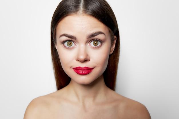 Primo piano della donna con gli occhi spalancati labbra rosse scoperte spalle