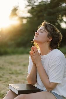 La donna chiuse gli occhi pregando in un campo durante il bellissimo tramonto le mani giunte nel concetto di preghiera per ...