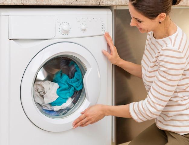 Donna che chiude la porta della lavatrice Foto Premium