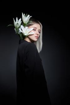 Colore capelli donna di una bionda con fiore di giglio su sfondo nero. colorazione capelli modello donna color cenere. ritratto di ragazza