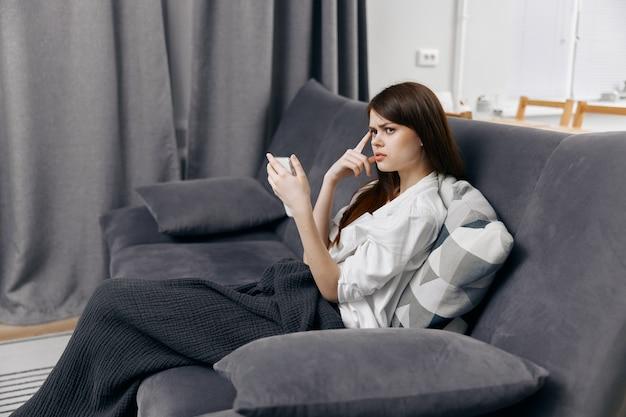 Una donna in un appartamento confortevole con un telefono cellulare in mano si siede sul divano