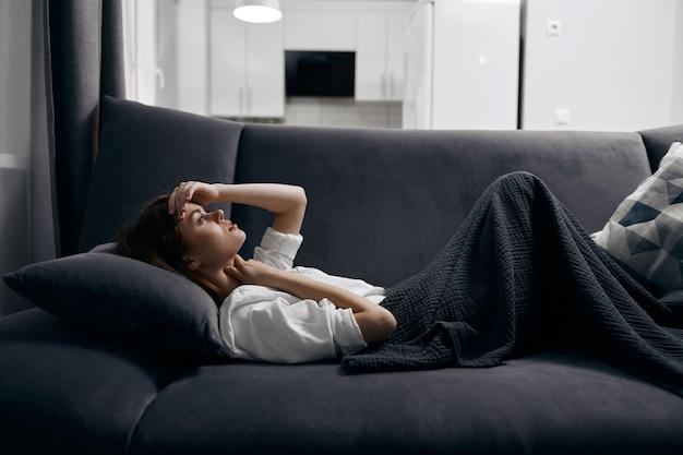 Una donna in una stanza confortevole giace su un divano coperto da una coperta grigia.