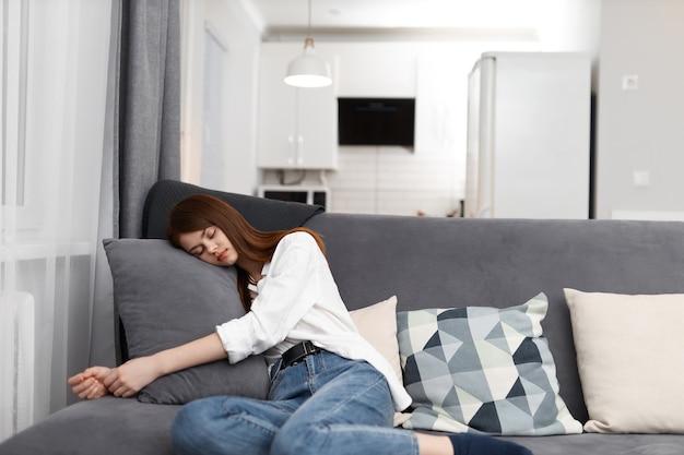 La donna si è comodamente sistemata sul divano dell'appartamento.