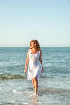 La donna che esce dal mare vestita di bianco
