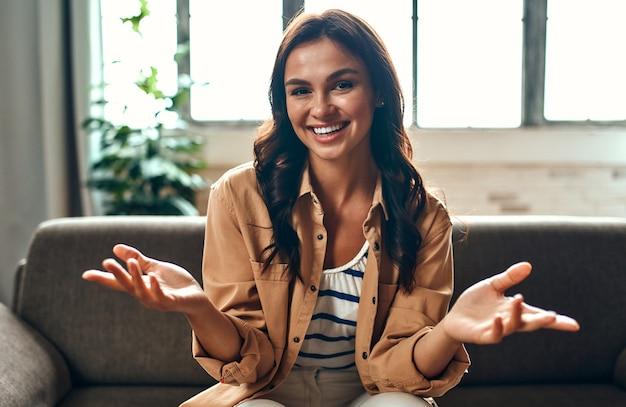 Una donna comunica in videochiamata mentre è seduta sul divano del soggiorno di casa. lavoro da casa.