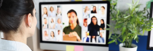 Donna che comunica con un gruppo di uomini d'affari tramite videoconferenza