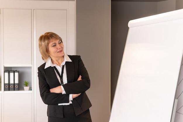 Una donna conduce un corso di formazione in un centro commerciale. donna di mezza età che insegna alla lavagna a fogli mobili in stile business.
