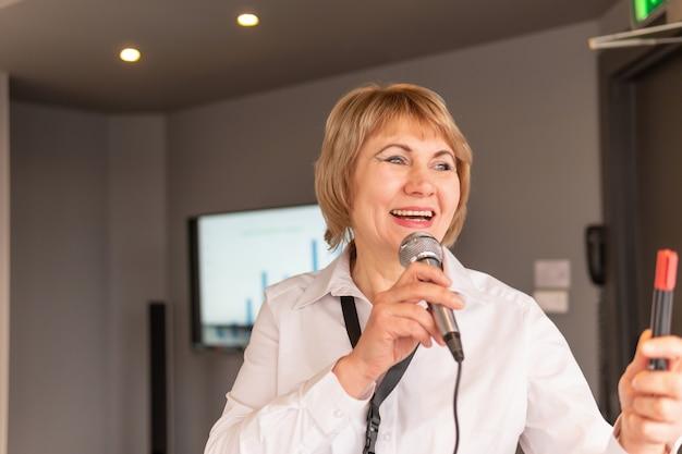 Una donna conduce un corso di formazione in un centro commerciale. donna di mezza età in un ufficio con un microfono