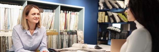 Consulente donna aiutando il cliente a scegliere le tende in officina cucito tende per ordinare il concetto