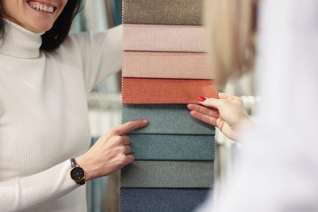La consulente donna mostra all'acquirente diversi tessuti tra cui scegliere dalla selezione del materiale per