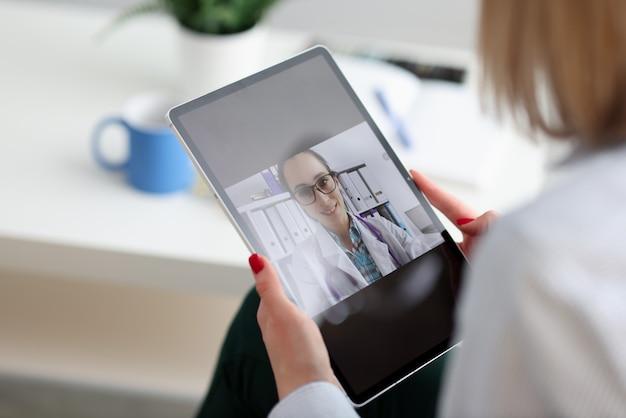 La donna si consulta con il medico via internet tramite videochiamata. concetto di assistenza medica a distanza