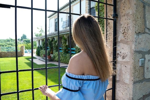 Donna che contempla dall'esterno della sua villa