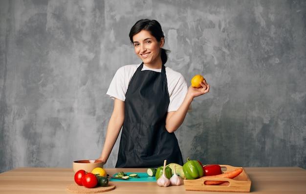 Donna cuoco grembiule nero affettare verdure tagliere cucina cucina cibo.