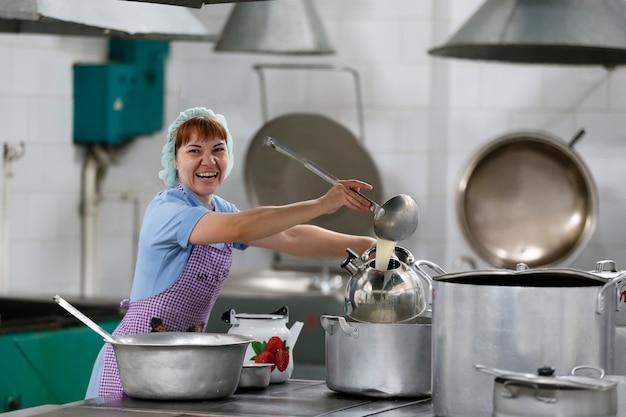 La donna cuoca in una cucina industriale versa un drink nel bollitore con una paletta grande e sorride