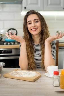 La donna che cucina la panetteria mangia, mescolando gli ingredienti: farina, uova, olio e altro.