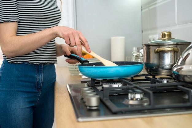 Donna che cucina cibo in cucina con padella sul piatto, cena deliziosa fresca. uno stile di vita sano