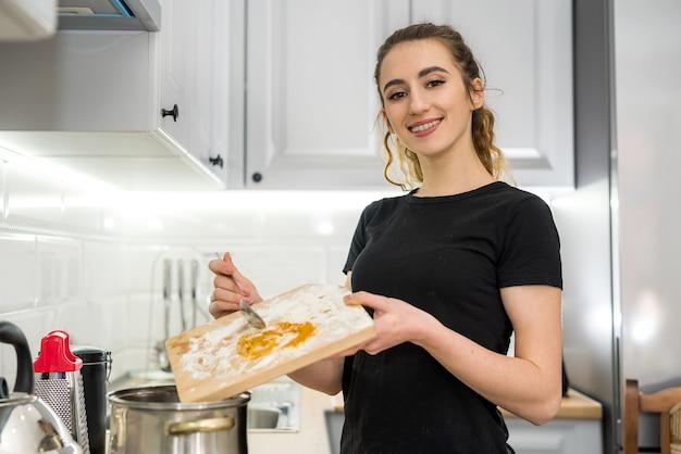Donna che cucina il cibo sulla cucina con padella sulla piastra