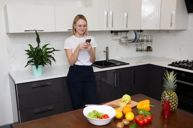 Donna che cucina a casa in cucina e alla ricerca di nuove ricette su smartphone