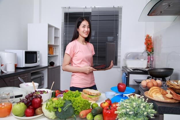 Donna che cucina e guardando con il portatile in cucina