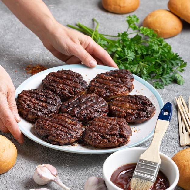 Donna che cucina hamburger di carne a casa in cucina
