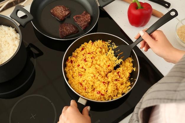 Donna che cucina il riso sulla stufa in cucina, primo piano