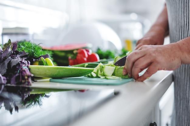 Donna che cucina le verdure in cucina.