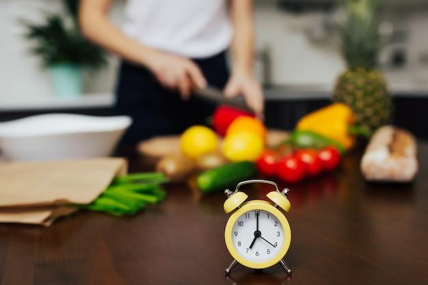 Donna che cucina insalata di verdure per cena focus sulla piccola sveglia gialla sul tavolo