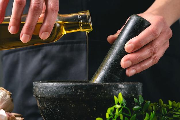Donna che cucina con olio d'oliva e mortaio in cucina