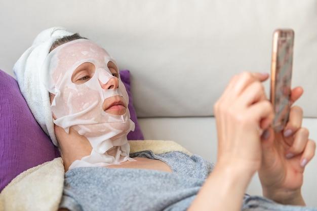 La donna nella maschera cosmetica con il telefono si trova sul primo piano del divano