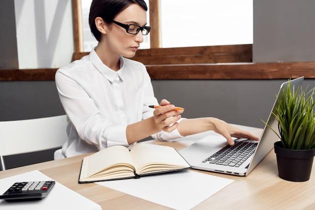 La donna in costume davanti al computer portatile documenta lo stile di vita professionale dello studio di lavoro
