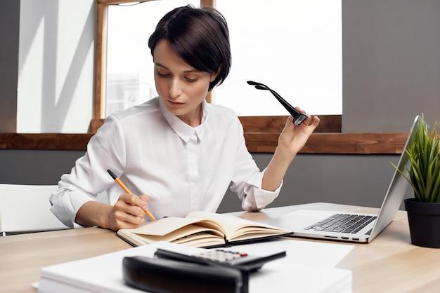 Donna in costume davanti allo sfondo chiaro esecutivo della segretaria del computer portatile