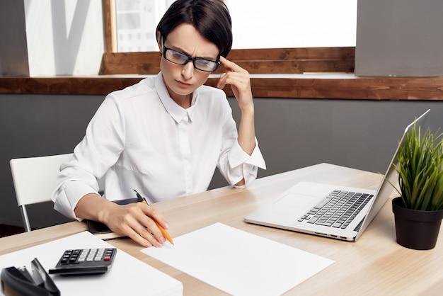 Donna in costume davanti allo stile di vita dello studio esecutivo della segretaria del computer portatile