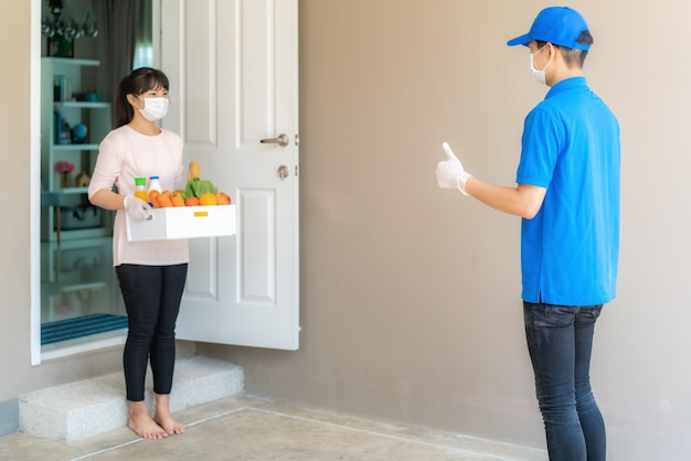 Cliente donna che indossa guanto e maschera per il viso riceve una scatola di generi alimentari di cibo
