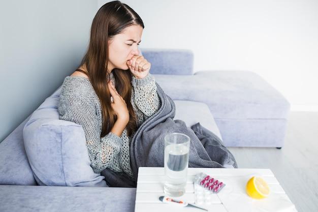 Donna che tossisce sul divano