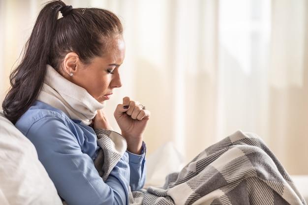 La donna tossisce a casa con mal di gola coperta da una coperta su un divano di casa.