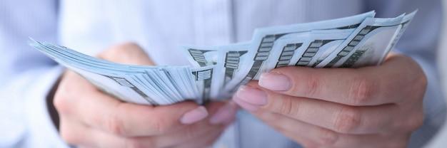 Donna che conta i dollari americani di valuta al primo piano del posto di lavoro.
